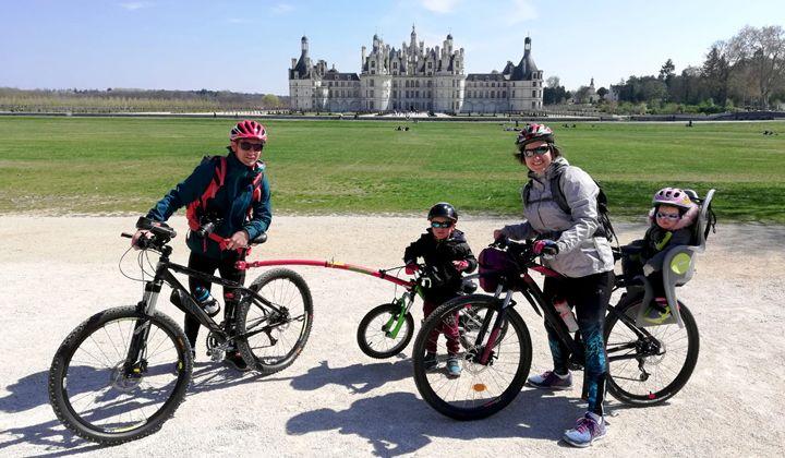 Famille à vélo devant le château de Chambord